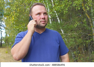 Young man smiling and talking on mobile phone in nature, green background. Communication without borders and outside the city.The unshaven man.