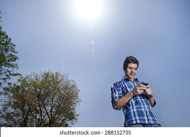 Young man smiling and text messaging