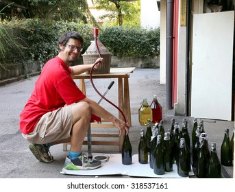 young man smiling while bottling the wine at home in glass bottles