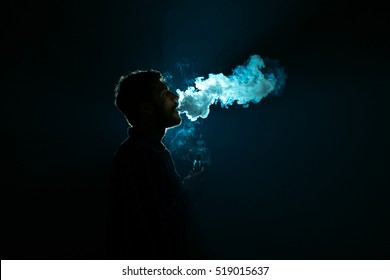 The young man smoke an electronic cigarette against the background of the bright light