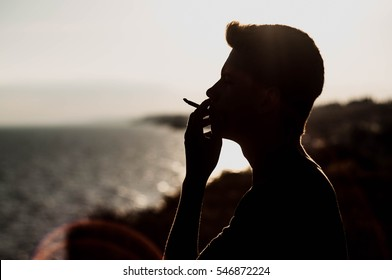 Young man smoking cannabis on the sea background