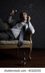 young man smoking cigar and drinking cognac at night