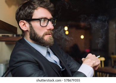 Young man smoking cigarette in the cafe