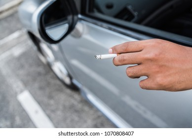 Young man smoking a cigarette in car.