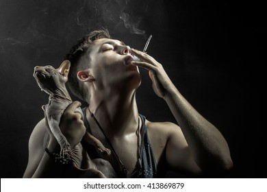 young man smoking cigarette holding cat breed Don Sphynx on his hands on black background