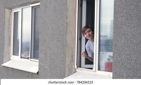 Young man smoking cigarette through the window of house. Man smoking by the window