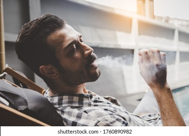 Young man smoking cigarette or tobacco. Guy addicted nicotine of cigarette and smoke a lot of tobacco. He smoke cigarette in public at outdoor. Cool guy blowing smoke of cigarette health care concept