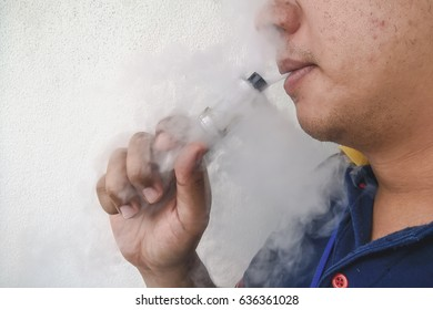 Young man smoking electronic cigarette. Background is white wall. World No Tobacco Day
