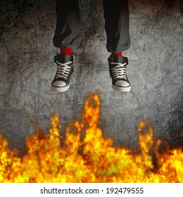 Young man in sneakers jumping over fire flames. Concept of recklessness and risk.