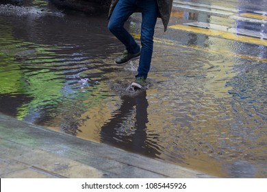 A young man in sneakers passes the road through a puddle after heavy rain. Hurricane, flood, flood.
