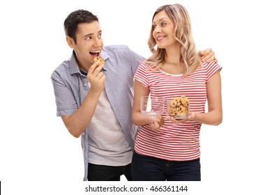 Young man sneaking up on his girlfriend and eating a cookie isolated on white background