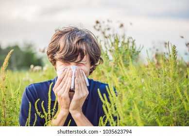 Young man sneezes because of an allergy to ragweed