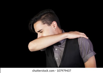 A young man sneezing into his elbow.  Black background.