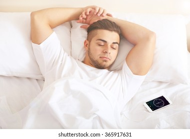 Young man snoozing on bed