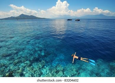 Young man snorkeling in clear shallow tropical sea over coral reefs