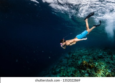 Young man snorkeling and skin diving over the coral reef edge in the tropical sea
