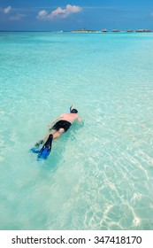 Young man snorkeling in tropical lagoon with over water bungalows