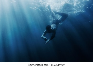 Young man snorkeling underwater, sea vacations.