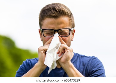 a young man snorts in a handkerchief