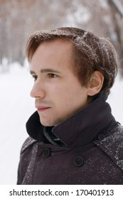 Young man with snowflakes in hair looks at distance outdoor at winter snowy day
