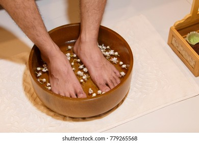 young man soaking feet in a bowl waiting spa staff to clean.