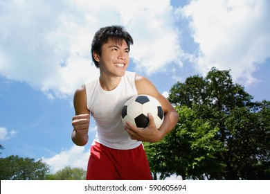 Young man with soccer ball, hand in a fist, smiling