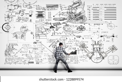 Young man solving math problema drawn on a white wall.