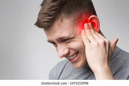 Young man with sore ear, suffering from otitis, black and white with red accent, free space