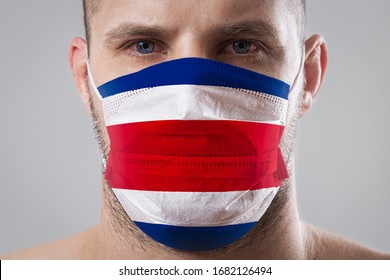 Young man with sore eyes in a medical mask painted in the colors of the national flag of Costa Rica. Medical protection against airborne diseases, coronavirus. Man is afraid of getting the flu