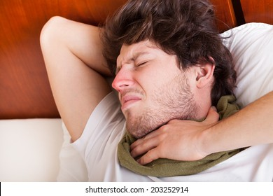 Young man with sore throat lying in his bed