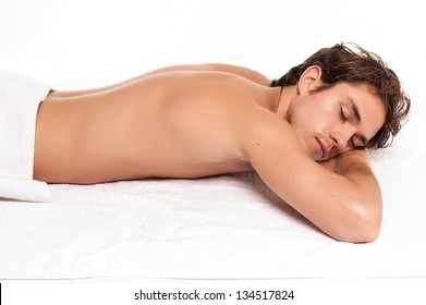 young man in a spa laying down. studio shot isolated on white.