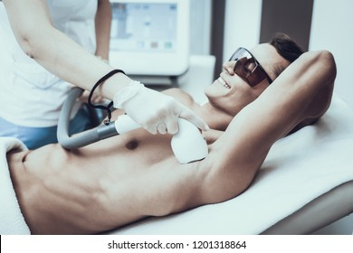 Young Man in Spa Salon for Laser Hair Removal. Guy in Beauty Salon. Modern Cosmetology. Proffesional Cosmetologist. Doctor with Laser Epilator. Men's Beauty Concept. Man in Glasses.