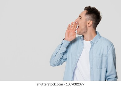 Young man speaker shouting speaking loud at copy space aside holding hand near open mouth making advertisement announcement concept isolated on white grey blank studio background, profile side view