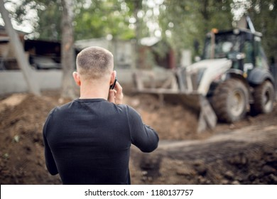 Young man speaks by phone on the construction site when the modern excavator performs excavation work on the construction site during reconstruction place