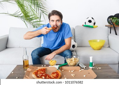 Young man sport fan watching match in a blue t-shirt eating pizza
