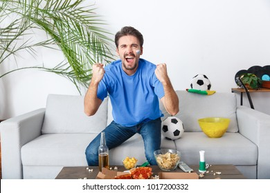 Young man sport fan watching match in a blue t-shirt victory
