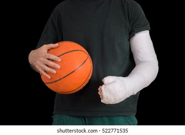 Young man sporting a bright white arm cast, holding a basketball after breaking his wrist in a basketball game fall, isolated on black