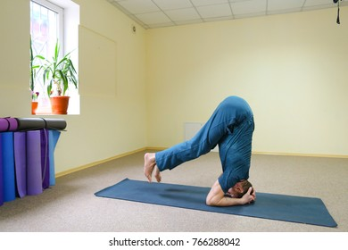 Young man sports athlete doing yoga sitting on floor in room. Building is spacious and light, on windowsill pots with flowers, under wall multi-colored rugs for fitness. Concept of importance of