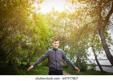 A young man in a sports jacket smiles and walks in the park on a summer day, hands to the side. Bright sun