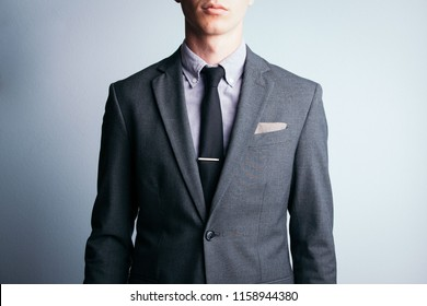 A young man sports a two piece, grey suit with a tie and pocket square. Dramatic lighting shows the details of his attire.