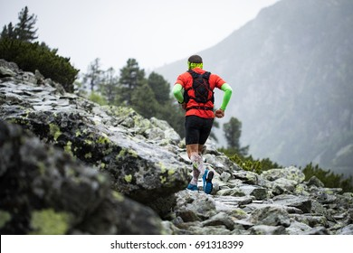 young man in sportswear with compress socks and backpack running on the mountain trail with bad rainy weather