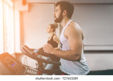 Young man in sportswear running on treadmill at the gym. Muscular bearded athlete during workout . Close up of young athletic female model trains at the indoor fitness center.