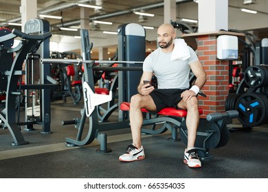 Young man in sportswear spending leisure in gym