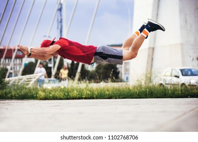 Young man in sporty wear alone working out doing extreme pushups