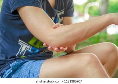 Young man sprained his arm and have elbow pain.Holding helpless his arm cubit