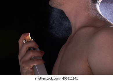 young man spray perfume on body isolated black