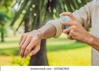 Young man spraying mosquito insect repellent in the forrest, insect protection