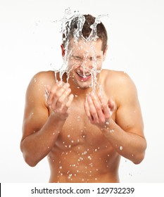Young man spraying water on his face after shaving / Young man splashing water on his face