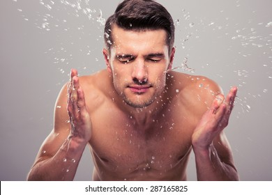 Young man spraying water on his face over gray background