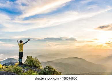 Young man is spreading his hand and thump up to the sun on top of mountain to enjoying valley view.
